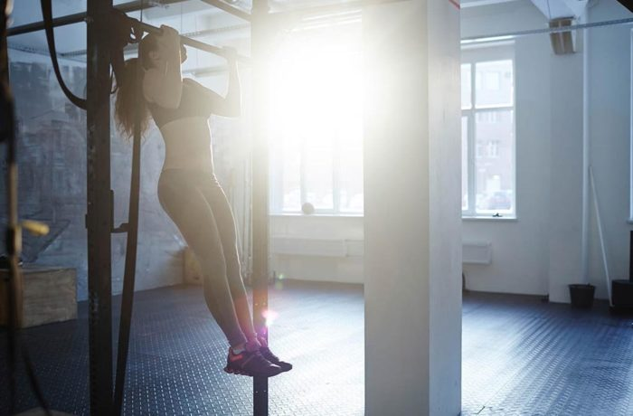 woman doing pull ups in a gym