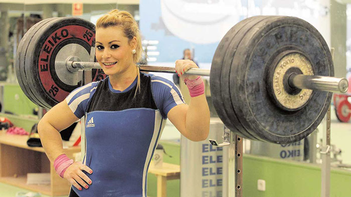 Lidia Valentin female weightlifter smiling and leaning against a barbell