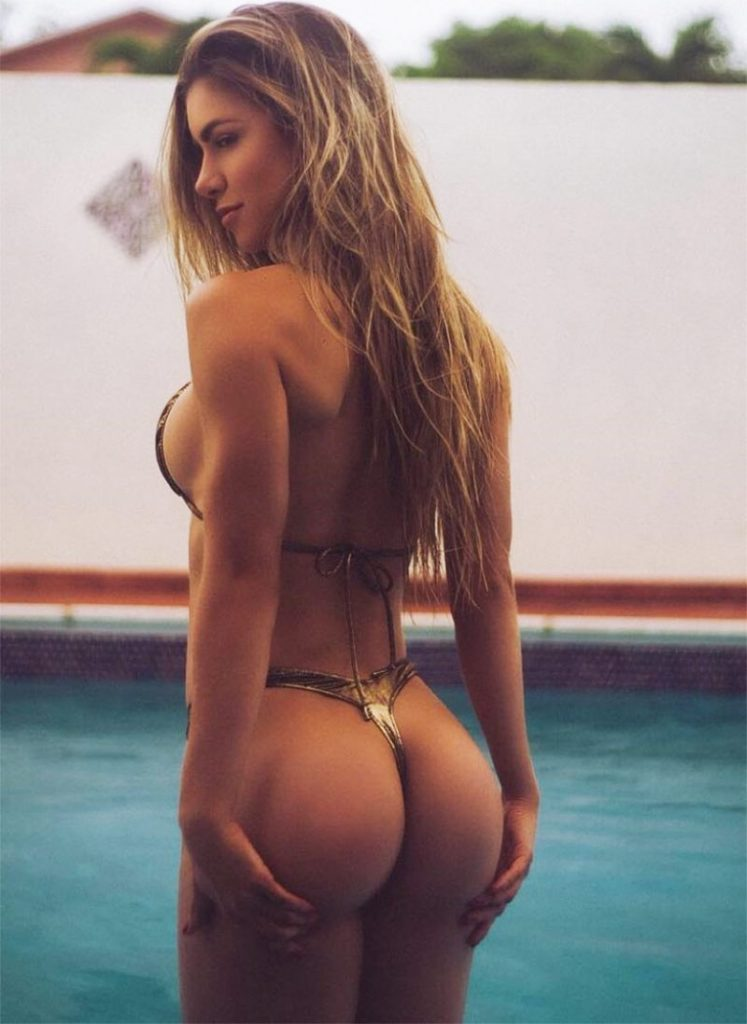 Anllela sagra posing in a pool in a bikini, showing off her amazing booty and figure.