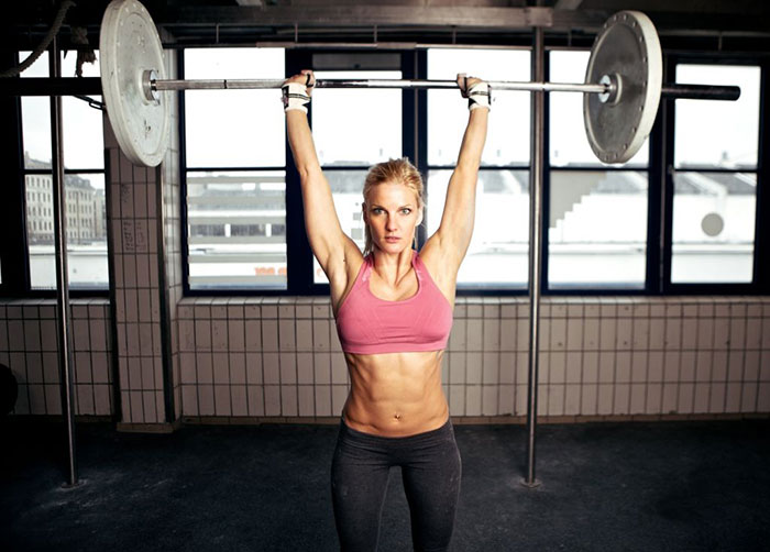 crossfit female athlete lifting a weight above her head