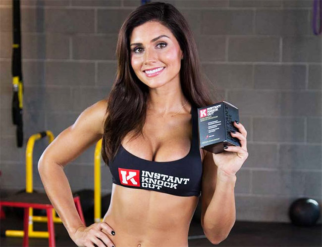 a picture of fitness model and queen of workouts alexia clark holding her favorite fat burner instant knockout