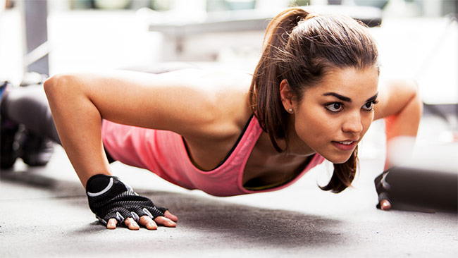 a girl performing push ups to get rid of her flabby arms