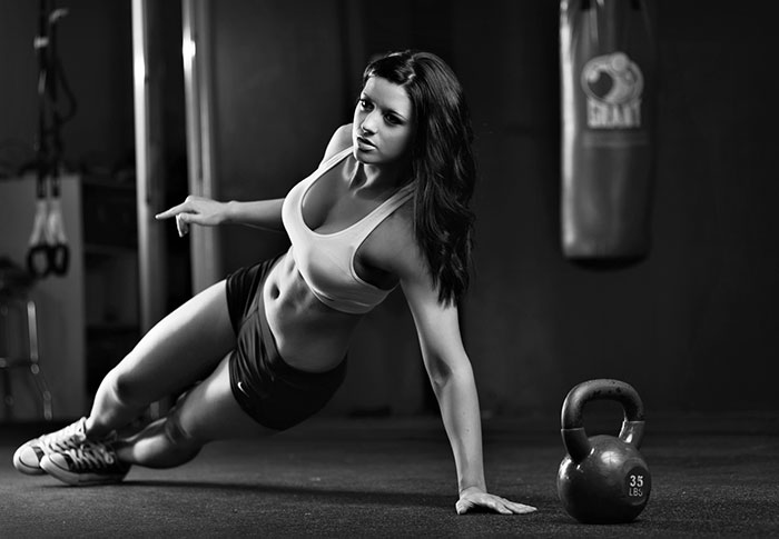 female weightlifter training in the gym training obliques