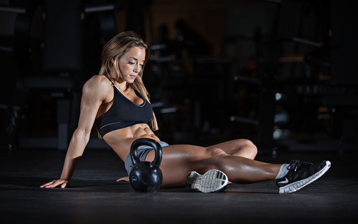 natural female weightlifter sitting on the floor after finishing her workout