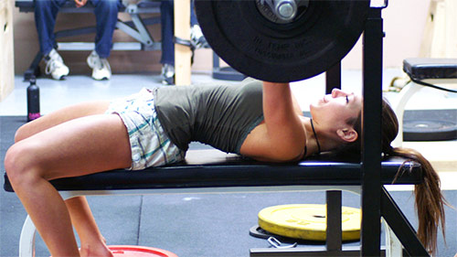 a girl performing bench press to tone up and lose weight