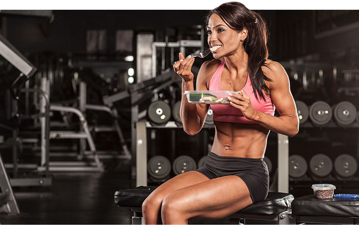 woman bodybuilder diet showing a woman sitting and eating a health meal looking lean and muscular
