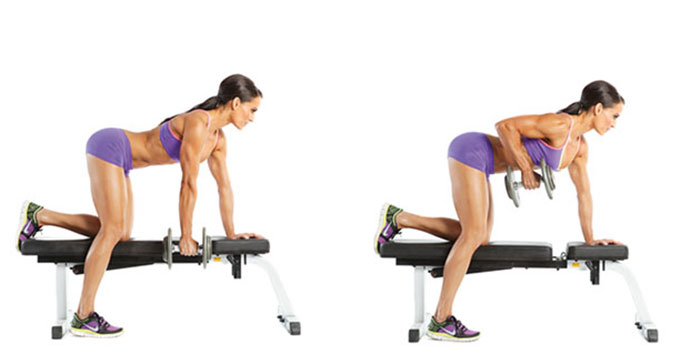 woman doing dumbbell row on a workout bench wearing gym clothes looking fit and lean