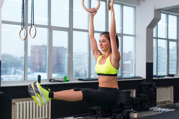 woman doing leg raises while holding gymnastic hoops in the gym looking lean and fit