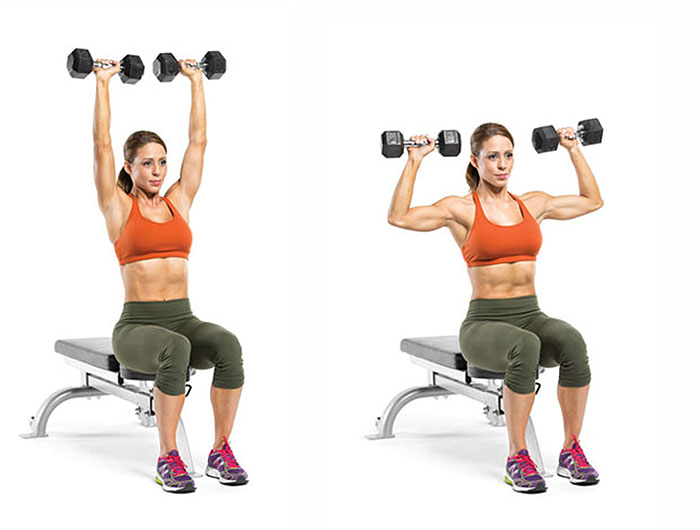 woman doing shoulder press with dumbbells while sitting on a bench