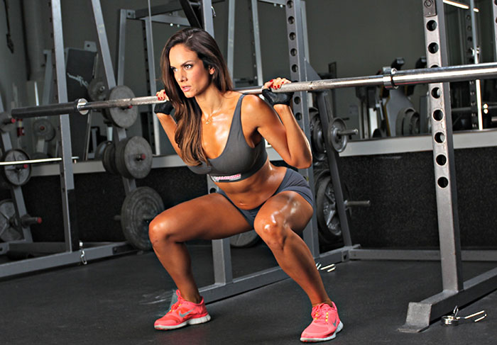 woman doing squats in the gym looking healthy and strong