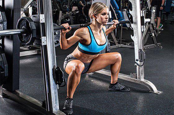 woman doing sumo squats in a squat rack