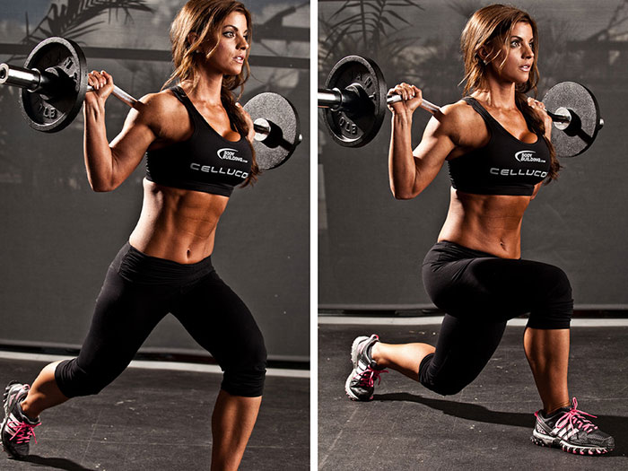 woman doing weighted lunges in teh gym with a barbell while looking lean and muscular