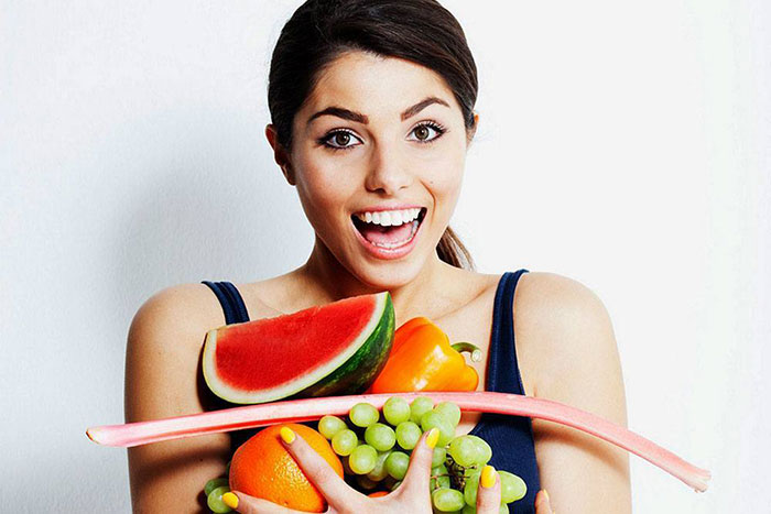 woman eating whole foods looking happy smiling building lean muscle