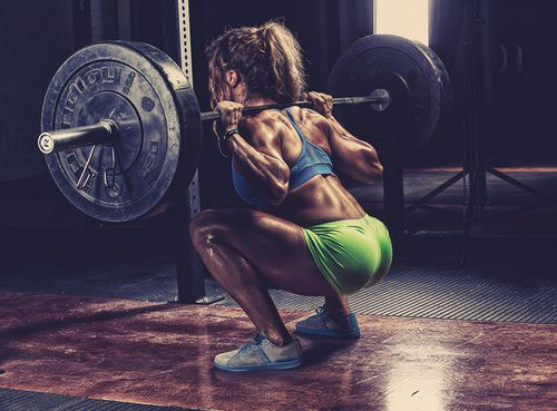 woman doing squats in the gym looking strong