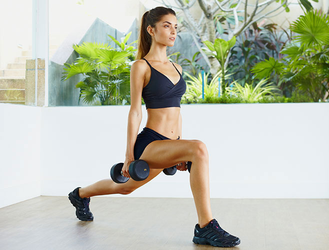 woman doing lunges with dumbbells