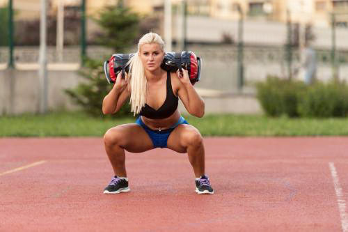 woman doing squats on a running track