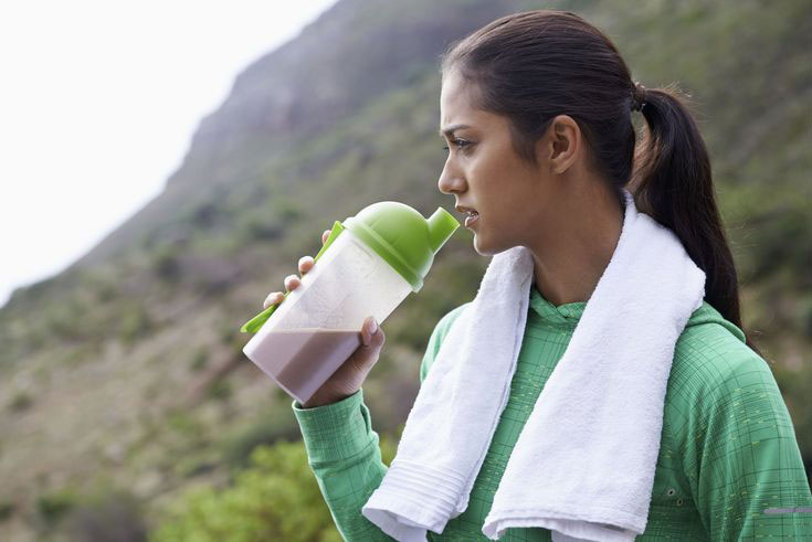 woman with protein shake drinking it looking into the distance