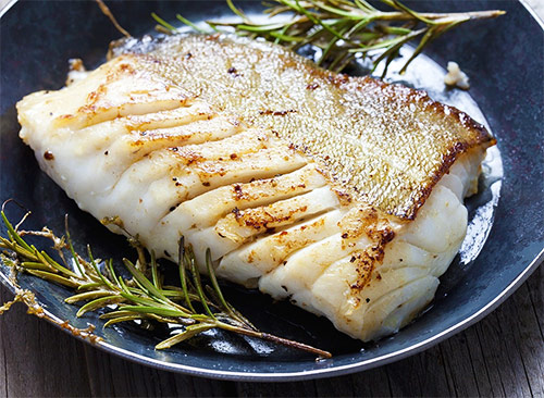 a fillet of cod cooked with herbs on a plate as a high protein source