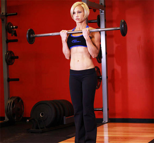 a female performing barbell curls as part of her bicep workout in the gym