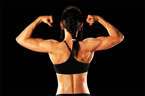 a female tensing her biceps during a workout