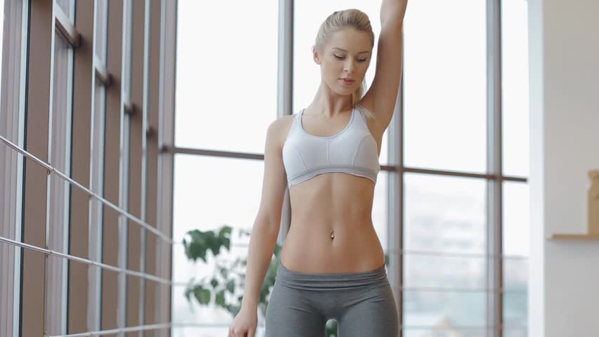 Blonde-haired woman exercising in her front room
