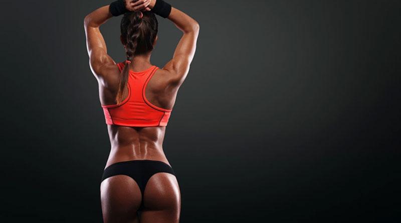 Female athlete in orange sports top on black background