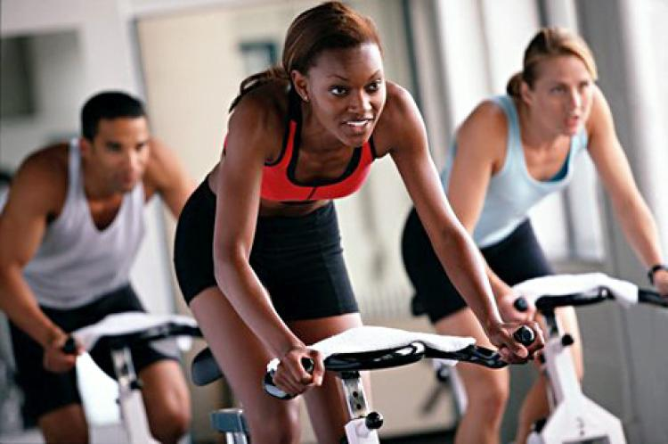 Group of women exercising on a bike in the gym