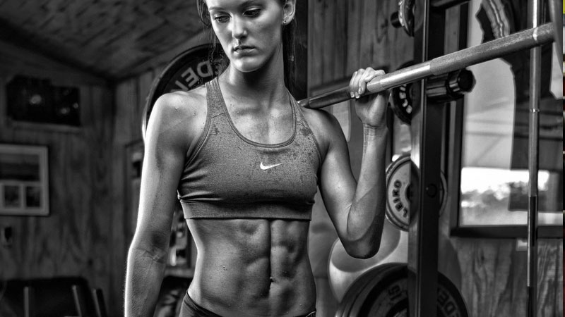 Young female athlete with muscle pump in the gym