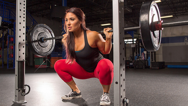 Dark-haired female athlete squatting in the gym