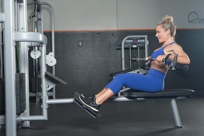 Niki performs cable row for Boss Shape & Burn workout