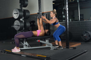 woman performs dumbbell press whilst being assisted