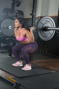 woman performs back squat for Boss workouts