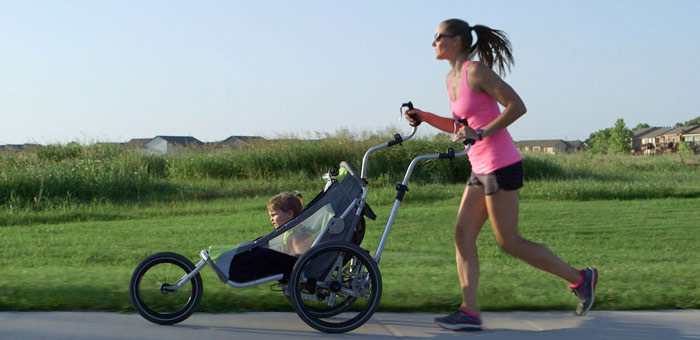 woman works out in park with jogging stroller