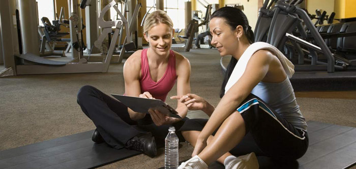 personal trainer gives feedback to female client
