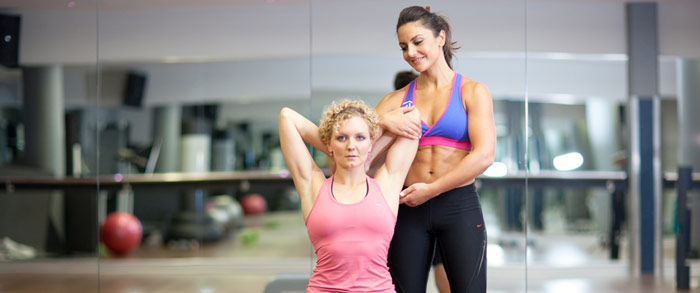 female personal trainer helps client maintain good form