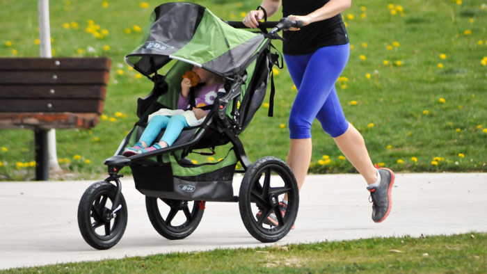woman runs with jogging stroller