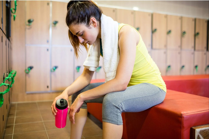 unmotivated woman in gym locker room