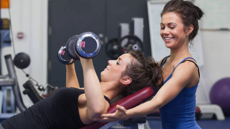 Female fitness trainer in the gym with a client