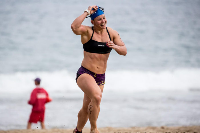 Kara Saunders (Webb) runs across sand during CrossFit games