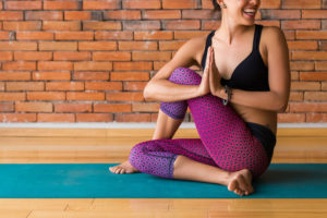 woman smiles in yoga pose