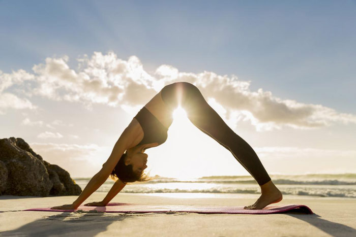 woman does downward dog yoga pose on a beach