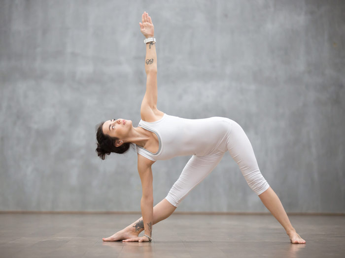 woman performs triangle yoga pose