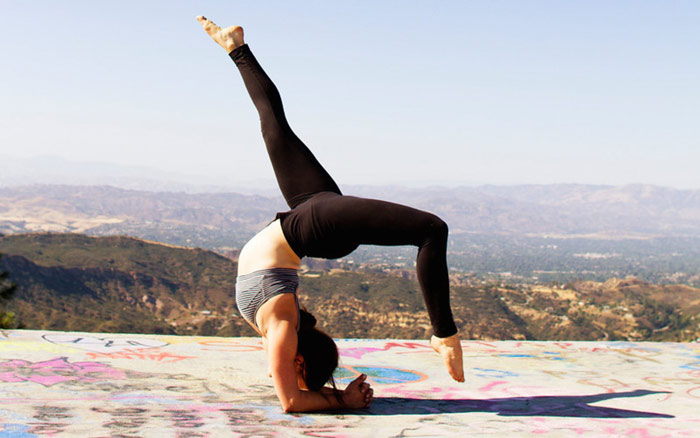 woman performs yoga pose with mountains in the background