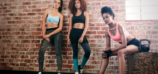 women standing together against a brick wall in a group workout for motivation