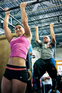 alternate grip pull up demonstrated by female crossfit athlete