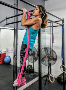 female athlete doing hockey grip pull up with rubber resistance band