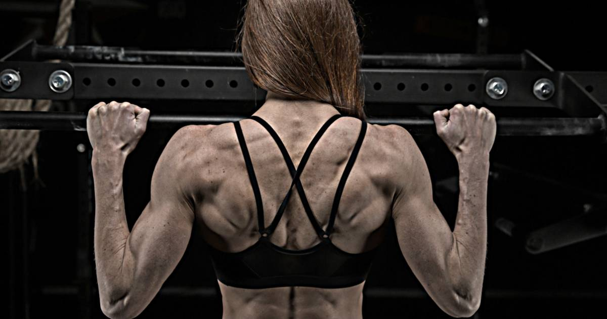 female performing pull up showing highly developed back muscles from ultimate program