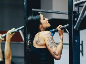 female athlete performing strict pull up