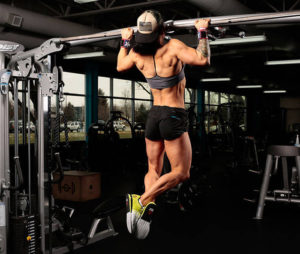 negative pull up demonstrated by muscular and sculpted female athlete