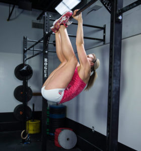 toes to bar being demonstrated by female crossfit athlete for ultimate pull up program
